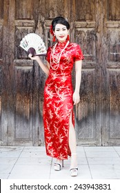 China Girl ,Chinese woman red dress traditional cheongsam ,close up portrait with old wood door
