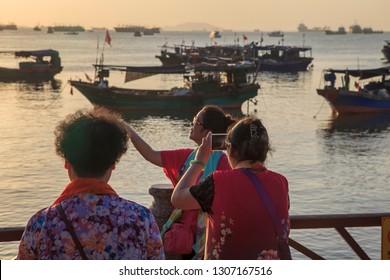 China, Hainan Island, Pheonix Island  - December 2, 2018: Panorama of Sanya City Bay, Bridge to Phoenix Island, chinese women taking selfie, editorial.