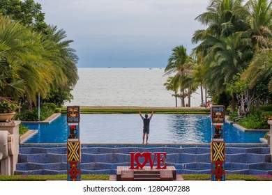 China, Hainan Island, Sanya bay - January 3, 2019. Celebration of St. Valentine's Day on the tropical islands. Inscription love on the background of exotic palms .a tourist who enjoys a view