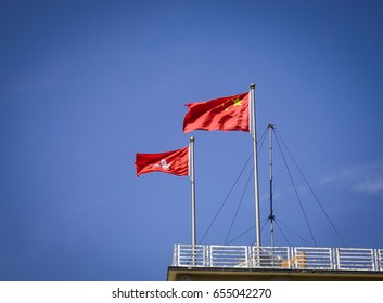China and Hong Kong flags floating on the top of government building at downtown in Hong Kong.