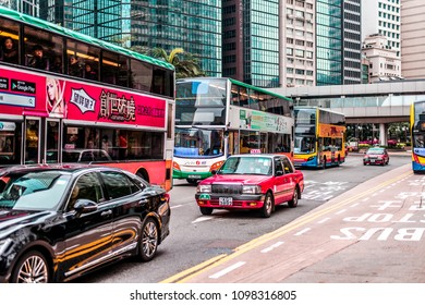 CHINA, HONG KONG - JANUARY 15, 2017: Traffic on the road in the downtown of Hong Kong, buses and taxis. Modern skyscrapers in the background.