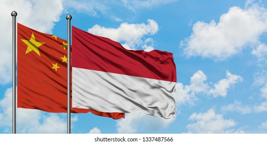 China and Indonesia flag waving in the wind against white cloudy blue sky together. Diplomacy concept, international relations.