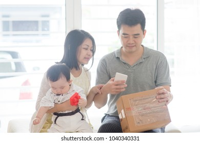 China man scanning QR code with smart phone. Happy Asian family at home, natural living lifestyle indoors.
