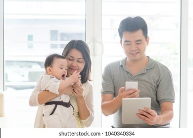 China man scanning QR code with smart phone. Asian family at home, natural living lifestyle indoors.