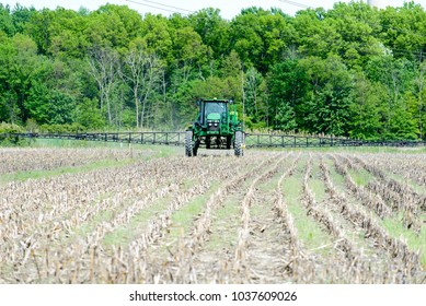 CHINA, MI, USA / JUNE 03, 2017: A self  propelled crop sprayer applies herbicide to a no till corn stubble field in China, MI on June 03, 2017. This treatment will control weeds.