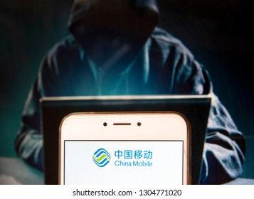 China Mobile logo is seen on an Android mobile device with a figure of hacker in the background.