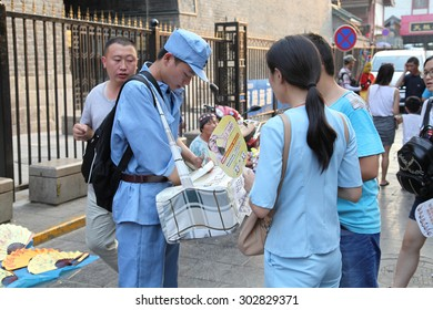 China. On July 29, 2015, xi 'an drum and hui street, in a special uniform of college students is to visitors from all over the world to sell old Popsicle. He is a work-study programs.