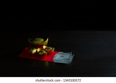 China piece gold and Red envelope money or gratuity in new year chinese called *Angpao* on brown wooden table background  / Select focus, Chinese Language, meaning rich and lucky space for texts