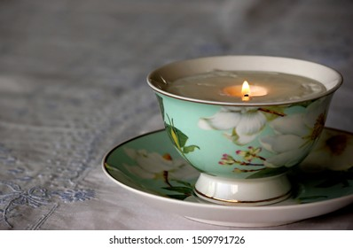 China tea cup with lit soy candle inside, resting on white embroidered linen tablecloth