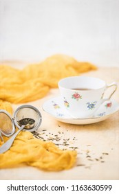 China Tea Cup and Saucer on Yellow Background; Loose Leaf Green Tea in Measuring Spoon; Tea Infuser Beside