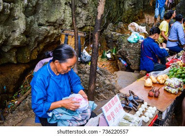 """China Village Vendor Selling on Street, August, 2014, Guizhou, China. The Chinese on white board means """"Miao ethnic minority Cigarette, 10 Chinese Yuan per pack""""."""