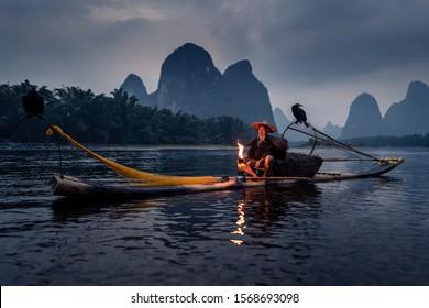 China Xingping, Nov 2019: Cormorant fishermen at the river side at dusk