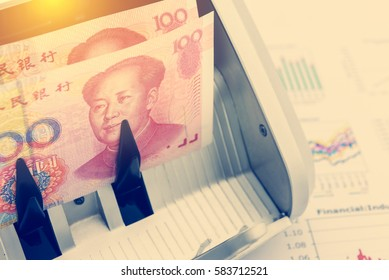China yuan 100 bill and a portrait of Mao Zedong on a bill counter with a magnetic counterfeit detection system. Used for China economy related i.e. gross national product, GDP per capita, labor cost.