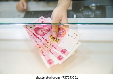 China yuan (CNY), China money, Women giving money currency of China. Exchange money for China yuan, business and finance concept.