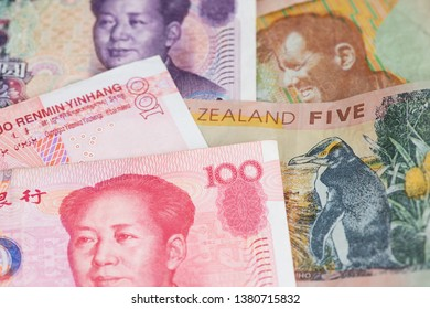 China Yuan Renminbi currency and New Zealand Dollar banknotes. Economic and political concept.