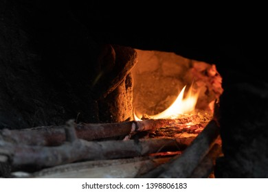China-Sichuan - 12/30/2018:  The kitchen in the village used to cook the dishes is putting the wood into the fire.