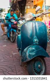 CHINATOWN, BANGKOK, THAILAND - Feb 2, 2019: Old motorcycle and shops on Yaowarat road, the main street of China town