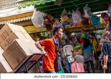 CHINATOWN, BANGKOK, THAILAND - Feb 2, 2019: Asain worker pushing shopping cart and shops on Yaowarat road, the main street of China town