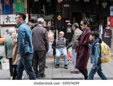 CHINATOWN, MONTREAL, CANADA - CIRCA OCTOBER 2016: Senior chines people seen talking to a shop owner in downtown Chinatown with members of the public passing by.