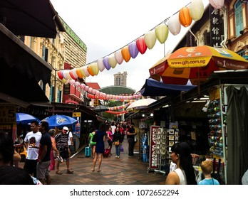 Chinatown, Singapore - December 14, 2013: Tourists shopping at traditional Chinatown market place surrounded with heritage Chinese buildings, authentic food places, gift shops.