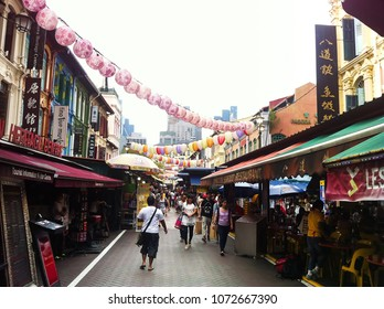 Chinatown, Singapore - December 14, 2013: Tourists walking, and shopping at traditional Chinatown market place surrounded with heritage Chinese buildings, authentic food places, gift shops.