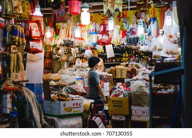 Chinatown, Singapore - December 27, 2015: One woman in a market stall full of nonperishable foods on the wet market in Chinatown, Singapore.