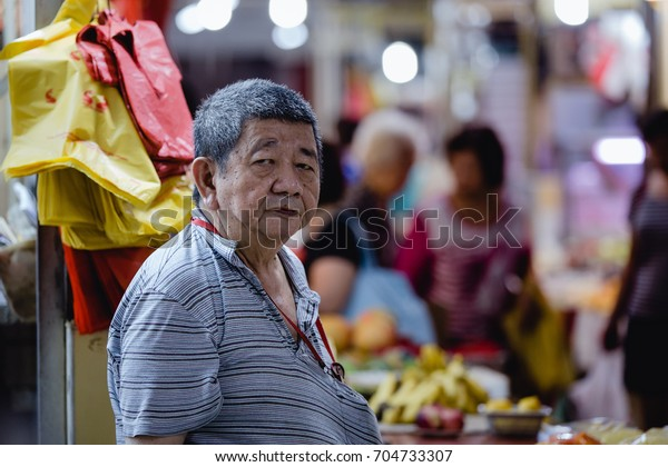Chinatown, Singapore - December 27, 2015: One old market vendor standing in front of his stall inside of the wet market in Chinatown, Singapore.