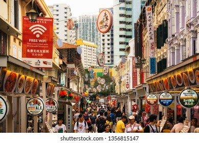 Chinatown, Singapore - February 8, 2019: Crowded street with street food in Chinatown against Central Business District in Singapore