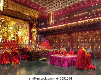 Chinatown, Singapore - January 27, 2017 : Buddhist monks in red and yellow ropes praying in the dharma hall of Buddha Relics temple