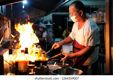 CHINATOWN, THAILAND - DEC 6: Chef cooking with fire on pan in the chinese restaurant in Bangkok Chinatown on December 6, 2018.  Wok on fire is very famous style of cooking.