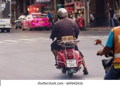 Chinatown (Yaowarat), Bangkok, Thailand - June 30, 2017 A man riding his red Vespa scooter carrying a parcel at the cross of the Yaowarat road (street), Bangkok, Thailand.