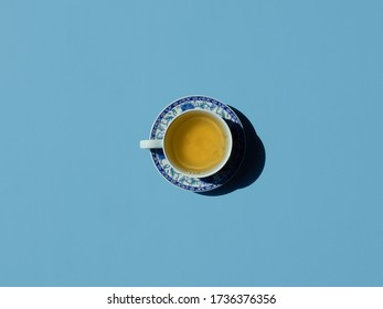 chinaware with green tea. top view on blue background. copy space