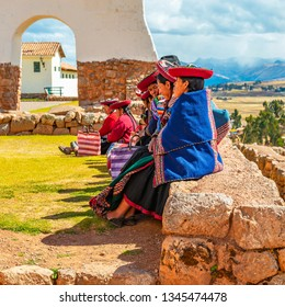 CHINCHERO, PERU - JUNE 23, 2013: A group of Peruvian Quechua indigenous women sitting on an ancient Inca wall in the archaeological inca ruin of Chinchero, Cusco Province, Peru.
