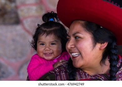 Chinchero Peru -May 18 : Portrait of a loving mother carrying her baby on her back in traditional native Quechua clothing. May 18 2016, Chinchero Peru.