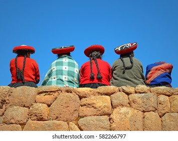 CHINCHEROS, PERU - JUNE 23 2013: A group of indigenous Quechua ladies having a conversation on an ancient Inca wall.
