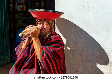 CHINCHEROS, PERU - SEPTEMBER 15, 2018: A Quechua horn blower with traditional clothing, hat and poncho in the city center of Cusco, Peru.