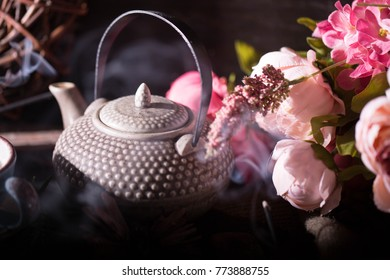 chineese teapot and flowers on a dark background and smoke