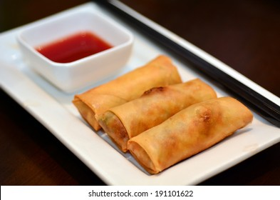 Chines food, Egg rolls served on a plate with chopsticks and Sweet and spicy hot sauce dipping.