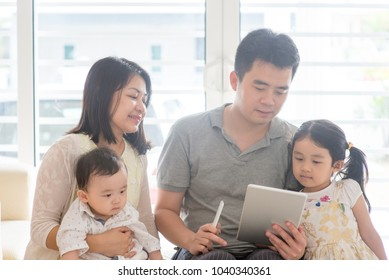 Chinese adult scanning QR code with smart phone. Asian family at home, natural living lifestyle indoors.