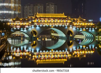 A chinese arch bridge ablaze with lights.