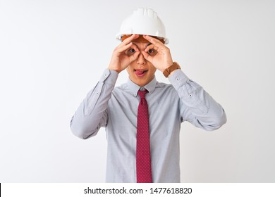 Chinese architect man wearing tie and helmet standing over isolated white background doing ok gesture like binoculars sticking tongue out, eyes looking through fingers. Crazy expression.