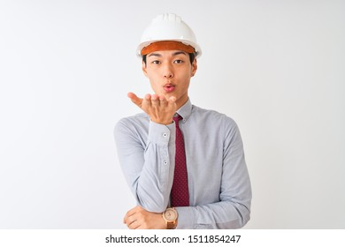 Chinese architect man wearing tie and helmet standing over isolated white background looking at the camera blowing a kiss with hand on air being lovely and sexy. Love expression.