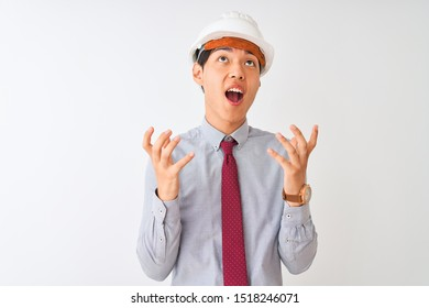 Chinese architect man wearing tie and helmet standing over isolated white background crazy and mad shouting and yelling with aggressive expression and arms raised. Frustration concept.