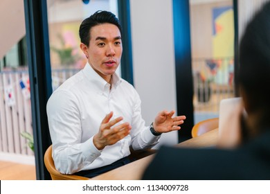 A Chinese Asian business man in a white shirt is having an animated discussion with an Indian Asian woman in a meeting room. He is young, handsome and professional and is interviewing a candidate.