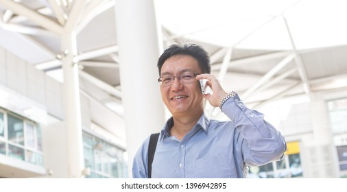 Chinese Asian businessman or executive talking on the smart phone with modern office background