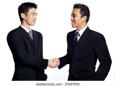 A Chinese, asian businessman shaking hands and smiling with an African business associate. Signifies the closing of deals. Shot in studio isolated on white