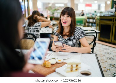 A Chinese Asian lady enjoys high tea with a good friend at a restaurant. She is beautiful, elegant and is smiling as she talks animatedly with her friend over cakes and tea on a weekend.