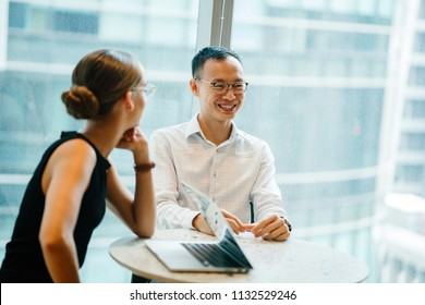 A Chinese Asian man and a Caucasian woman sit at a table and are having a light hearted business discussion during the day in their office. They are part of a diverse team.