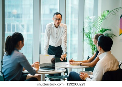 A Chinese Asian manager is speaking and conducting a meeting with his diverse team in a meeting room. He is confident and mature and is standing as he talks to his team who are sitting around him.