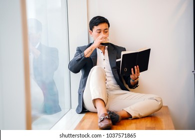 A Chinese Asian (Singaporean) professional man sits against the window and reads a book while he sips coffee. He is dressed in business casual in a suit with loafers and smiling.